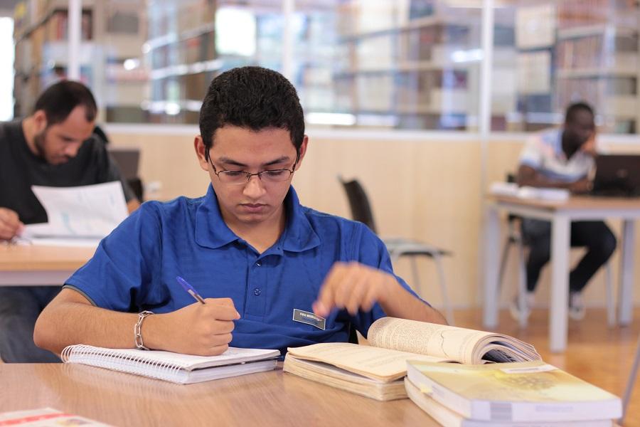 Aluno estudando na biblioteca